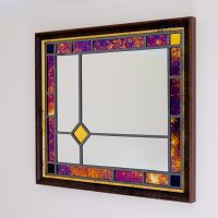 Framed stained glass mirror in purple and gold